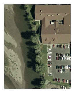 Part of a high-resolution orthophoto showing a stream, trees, building, and a parking lot