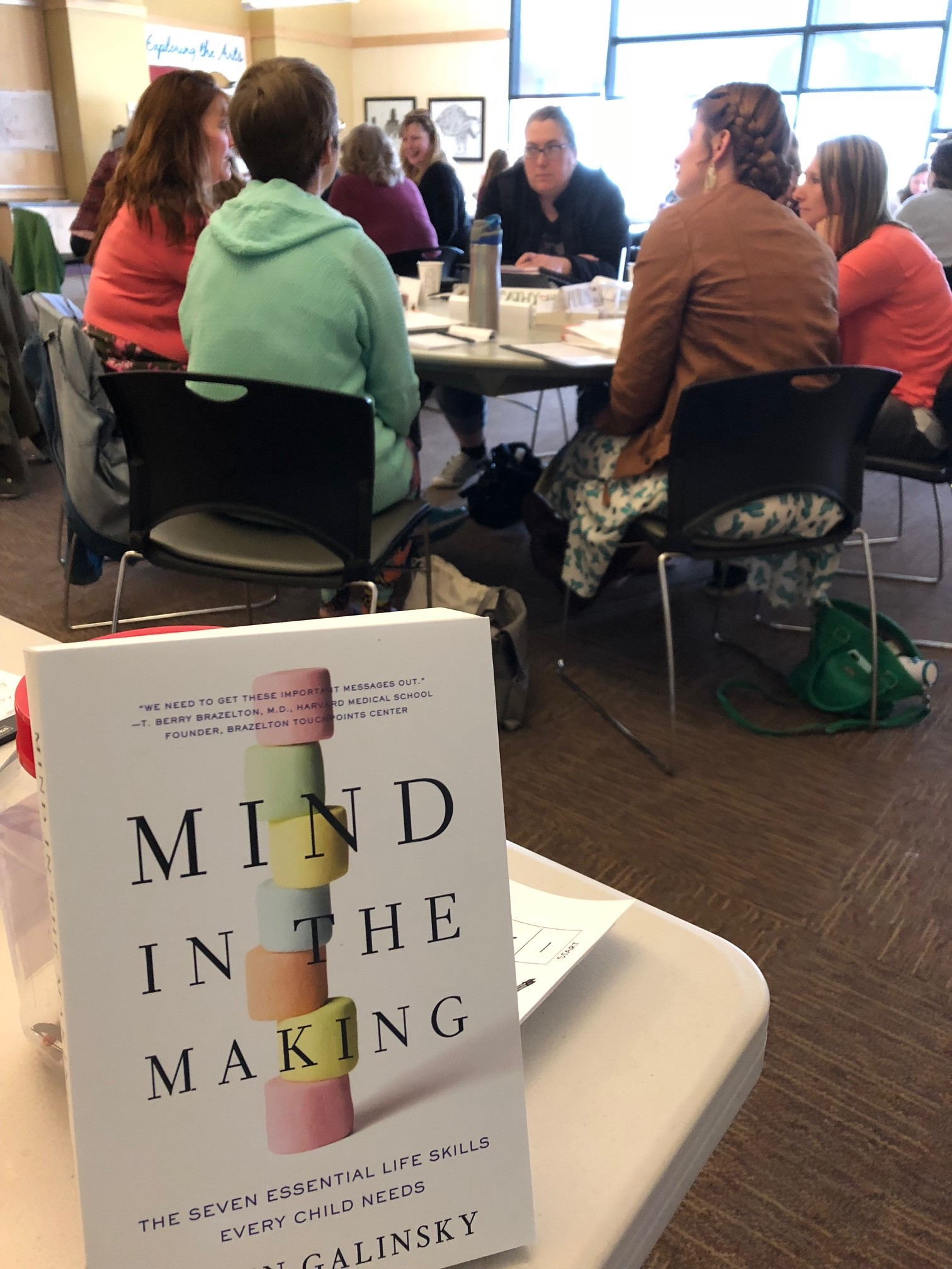 Mind in the Making Book with attendees hard at work learning in the background.